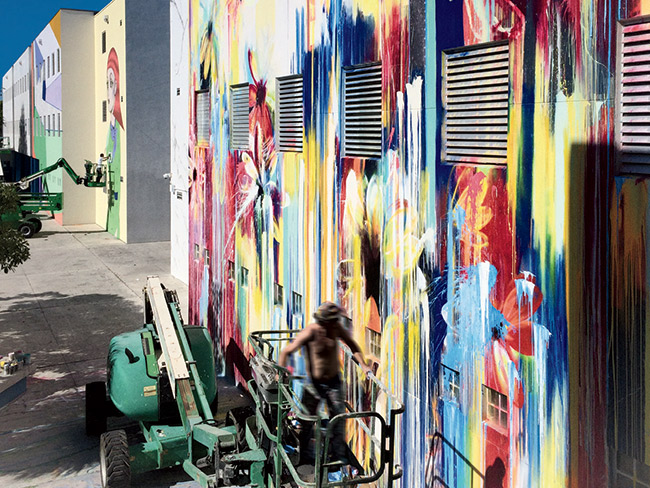 Miami-based artist Magnus Sodamin painting a wall in his signature floral explosions.